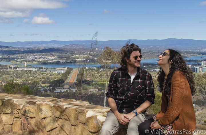 Pareja sonriendo en frente e la vista panorámica de la ciudad de Canberra en Australia