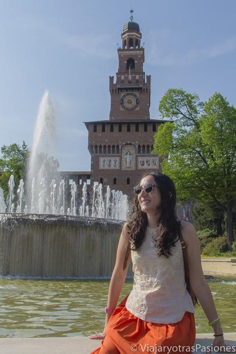 Sentada y alegre frente a el Castello Sforzesco en Milán en dos días en Italia