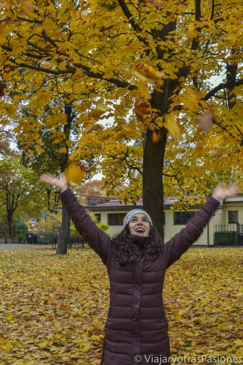 Jugando con hojas otoñales en los jardines Vermanes en Riga en Letonia