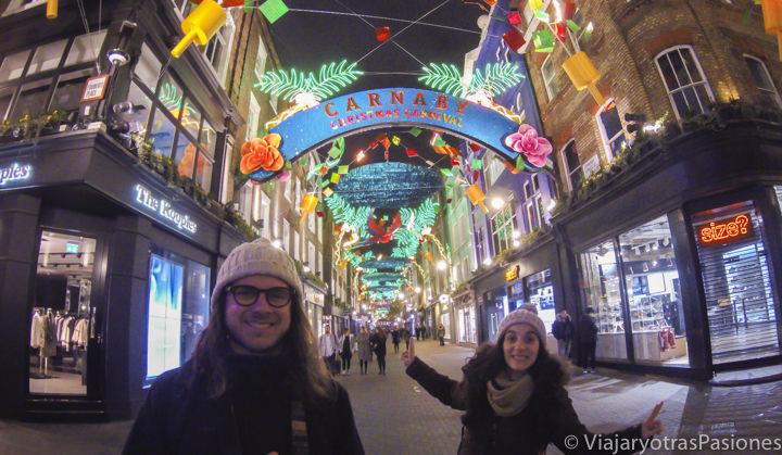 Pareja sonriente en Carnaby Street en la Navidad en Londres en Inglaterra