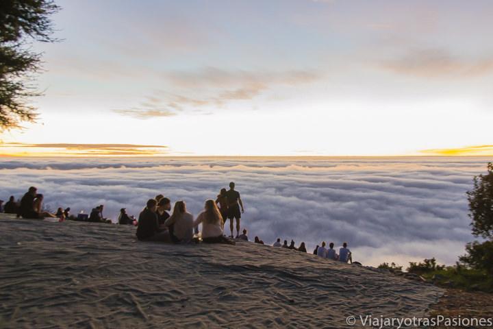 Gente sentada tranquilamente viendo el atardecer en Signal Hill en Sudáfrica