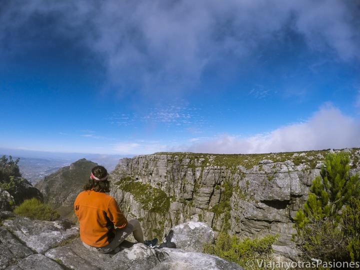 Sentado viendo el panorama en la cima de la maravillosa Table Mountain en Ciudad del Cabo en Sudáfrica