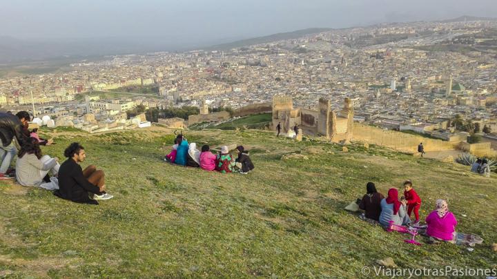 Gente sentada tranquilamente cerca de la Necrópolis de Merinide en qué ver en Fez en Marruecos
