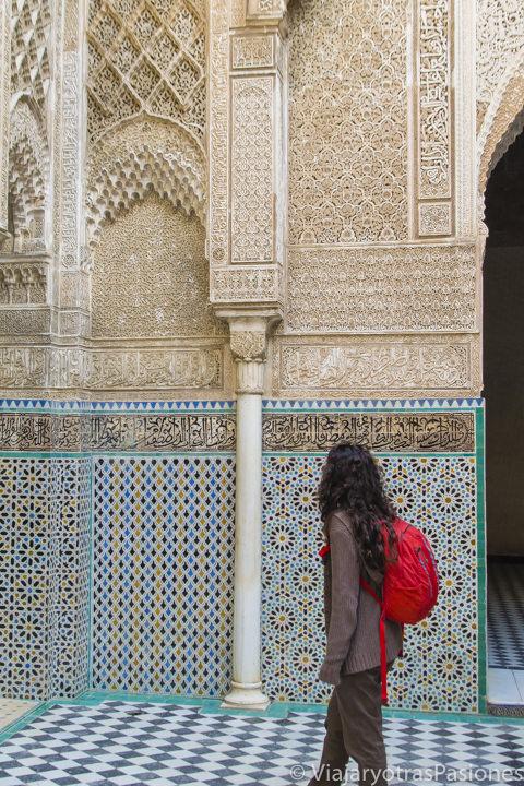 Mirando los preciosos detalles de la bonita madrasa Al Attarine en Fez en Marruecos