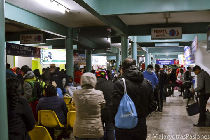Mucha gente en el interior de la estación de buses de Puno en Perú