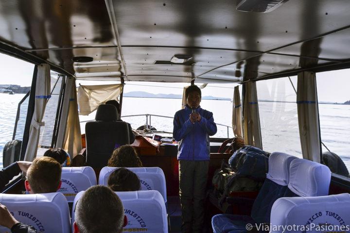 Interior del barco del tour y guía en el Lago Titicaca en Perú