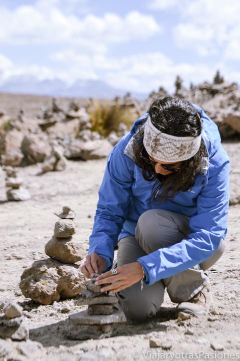 Colocando piedras en el mirador de los volcanes de Patapampa, cerca del canyon del Colca, en Perú