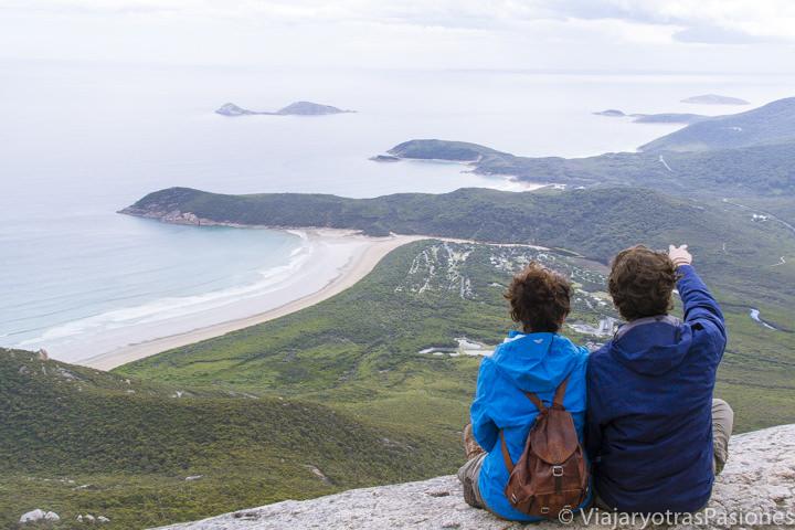 Pareja sentada con una hermosa vista del Wilsons Promontory y Tidal River en Australia