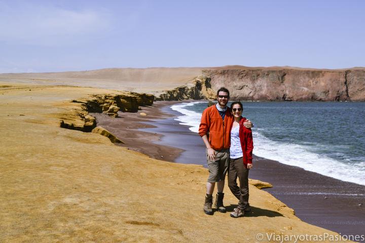Pareja en la hermosa playa roja en la Reserva de Paracas en Perú