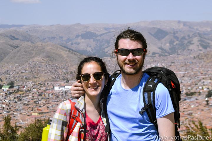 Pareja sonriente en el Sacsayhuaman y panoramica de Cuzco en Perú