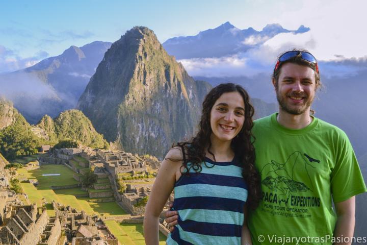 Pareja sonriente en el espectacular sitio de Machu Picchu en Perú
