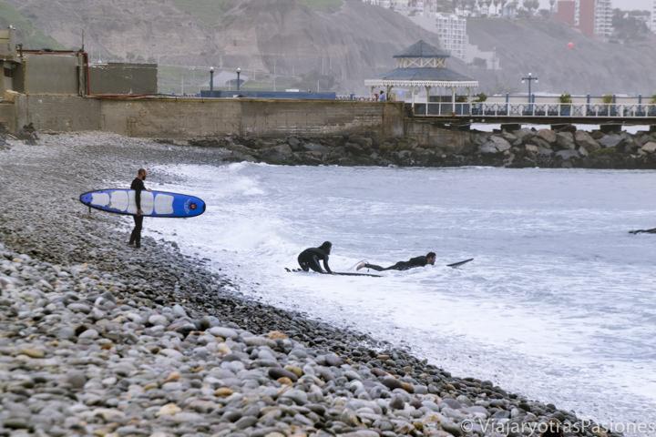 Grupo de surferos en el Pacífico en la playa de Miraflores, Lima