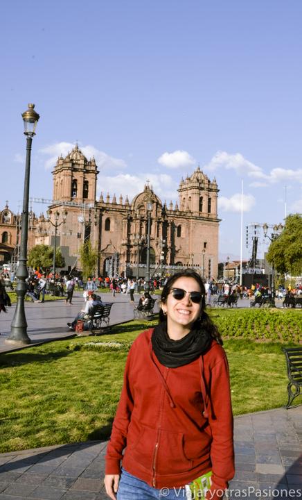 Sonriente en frente de la catedral de Cuzco en la Plaza de Armas en Perú