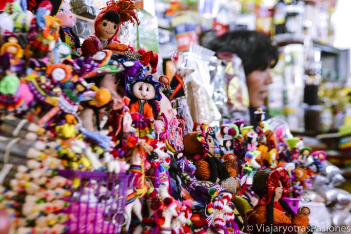 Artesania en el mercado de San Pedro con muñecos y muchos colores en Cuzco en Perú