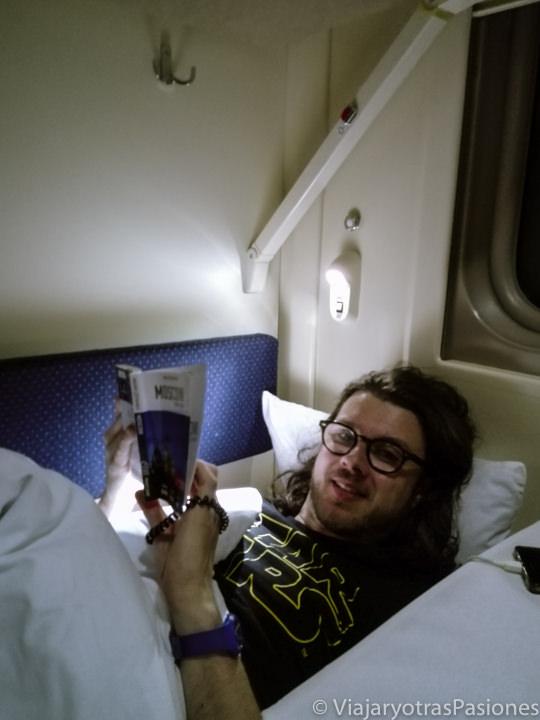 Acostado en una cama en la Flecha Roja en viaje entre Moscú a San Petersburgo en Rusia