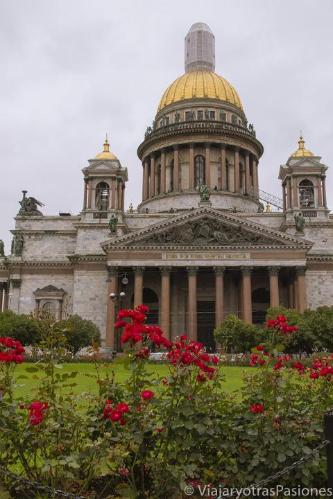 Flores y imponente fachada de la catedral de San Isaac en San Petersburgo en Rusia