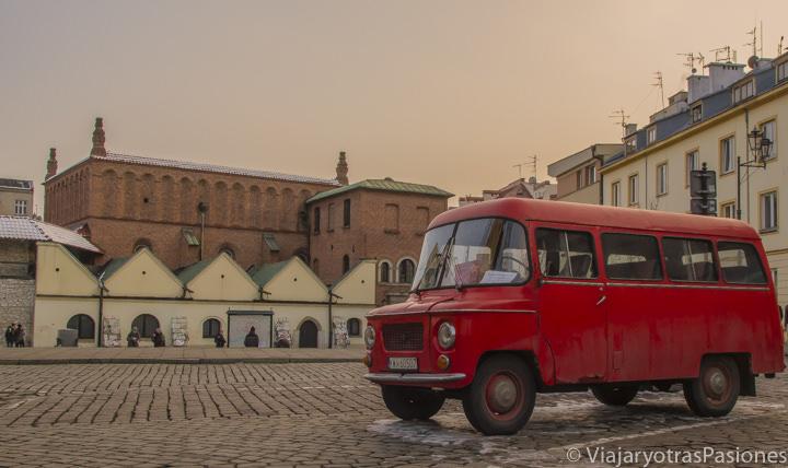 Camioneta roja vintage en la plaza de la antigua sinagoga en Cracovia, en Polonia