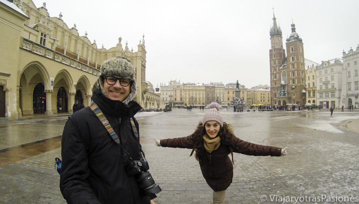 Pareja sonriente en la plaza del mercado en Cracovia en Polonia