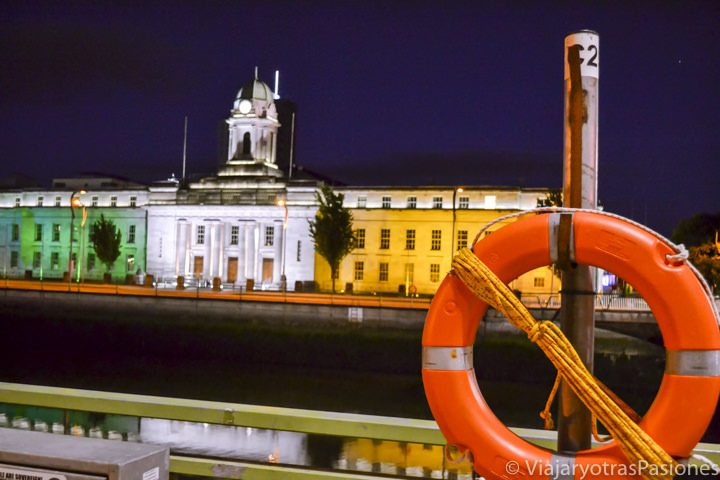 Imagen nocturna del ayuntamiento de Cork iluminado con los colores de la bandera de Irlanda