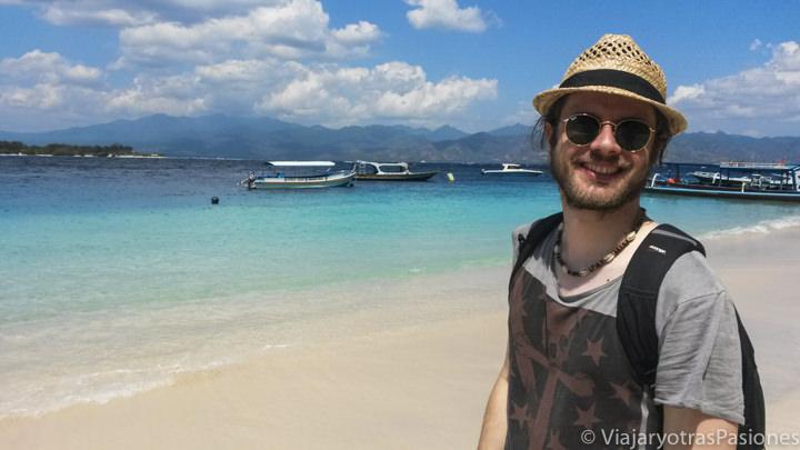 Feliz cerca de la agua turquesa de la playa de las Gili Islands, Indonesia