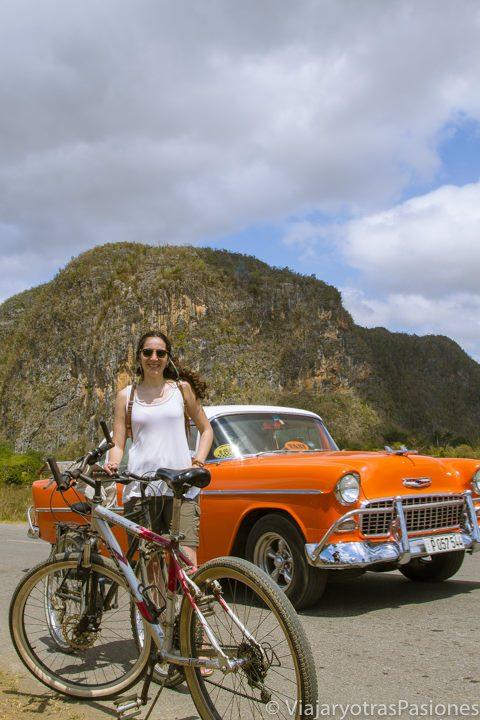 Paula en bici con un coche y un mogote detrás en Viñales en Cuba