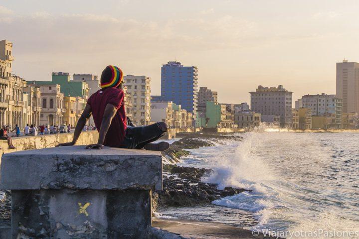 Un chico de espaldas, con gorro jamaicano, disfruta del atardecer en el malecón de La Habana, Cuba