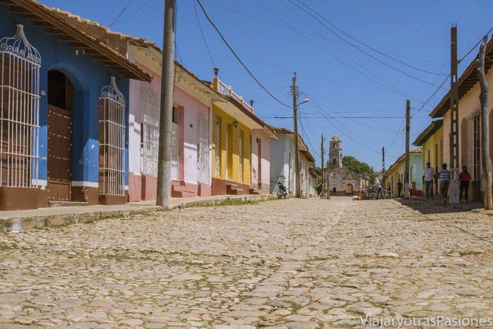 Típica calle cubana con suelo empedrado y casas bajas de colores. Al fondo, la iglesia en ruinas de Santa Ana