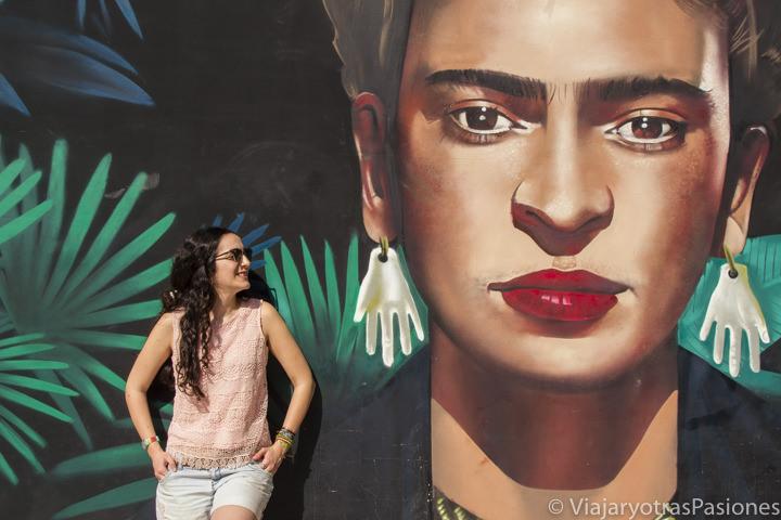 Posando frente al famoso mural de Frida Khalo en Playa del Carmen, México
