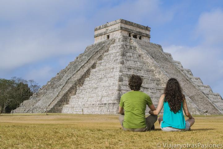 Pareja sentada mirando la hermosa piramide de Chichen Itza, México