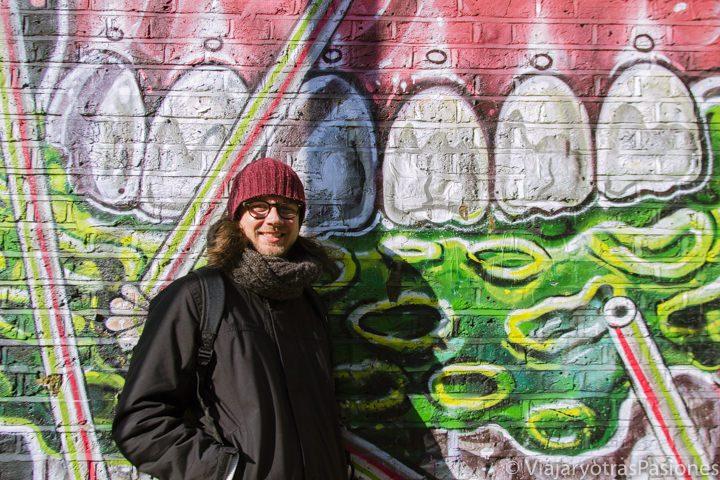 Feliz frente a un famoso murales de street art en Brick Lane, en Londres