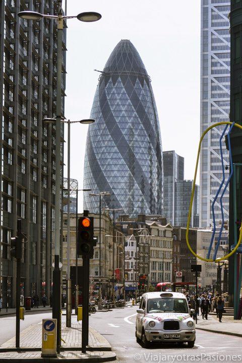 Un taxi gris circula por la City de Londres cerca del famoso rascacielos Gherkin