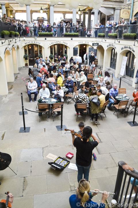 Escuchando música en el patio del mercado de Covent Garden, Londres