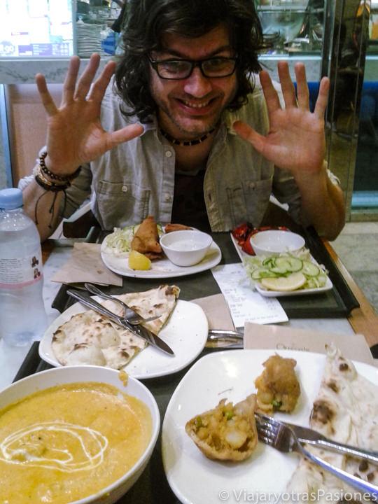 Comiendo típica comida indiana en un barrio de Londres, Inglaterra