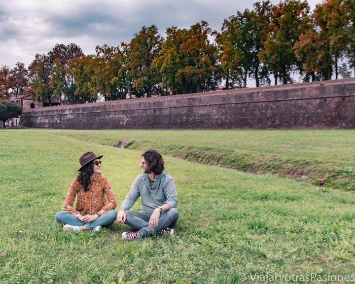 Pareja frente a la famosa muralla de Lucca en Toscana, Italia