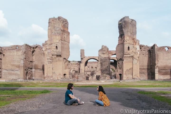 Pareja frente a las increíbles Termas de Caracalla en Roma, Italia
