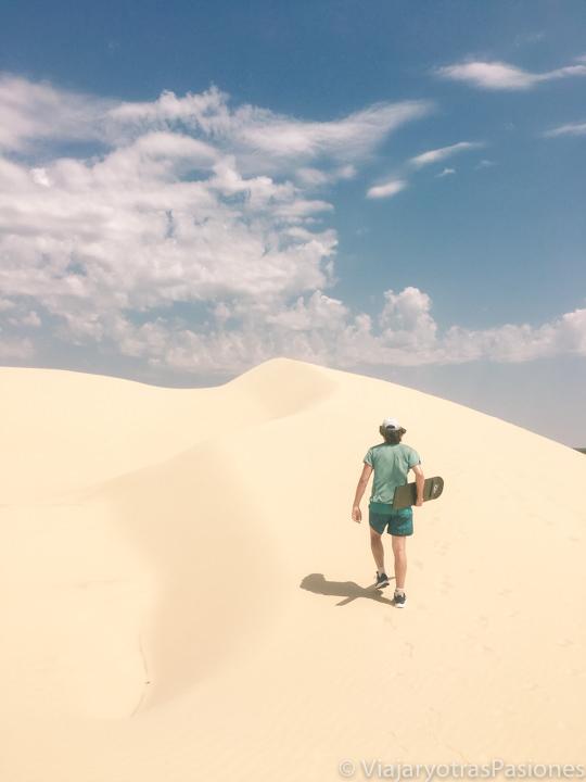 Subiendo una de las dunas de Stockton Beach para hacer sandboarding, en Port Stephens