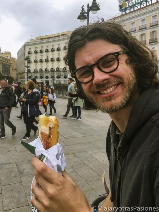 Comiendo un bocata de jamón en Puerta del Sol en Madrid, España