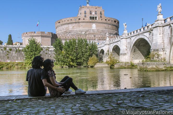 Pareja frente el hermoso Castel Sant'Angelo y del río Tiber en el centro de Roma, Italia