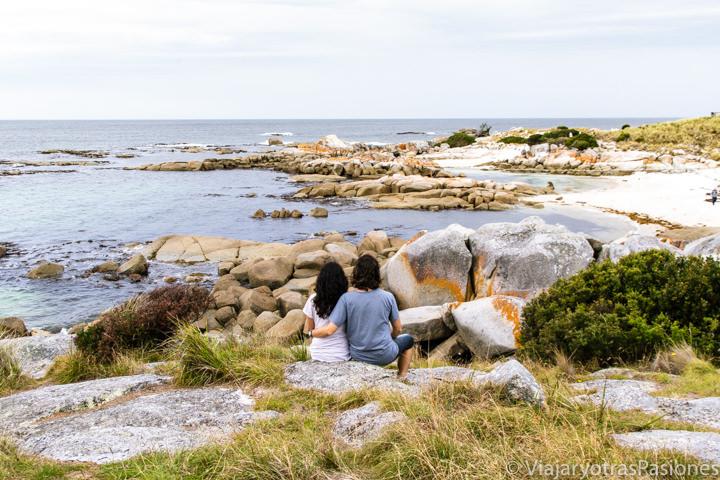 Pareja mirando il maravilloso paisaje de la Bay of Fires en Tasmania, Australia