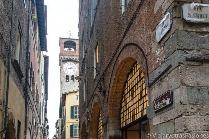 Entrada de la famosa via Fillungo y vista de la Torre delle Ore en Lucca, Italia