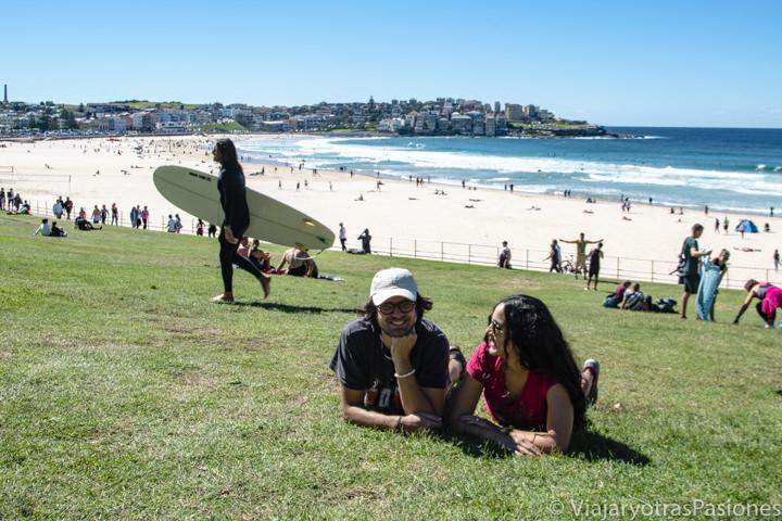 Pareja posando frente a la famosa playa de surf en Bondi, Australia
