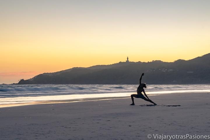 Haciendo yoga al amanecer en la bonita playa de Byron Bay en Australia