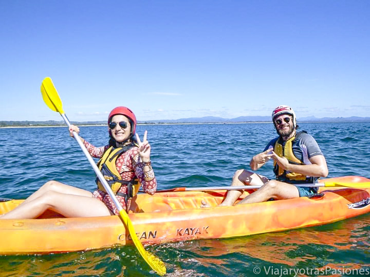 Pareja haciendo kayac en el oceano frente a Byron Bay en Australia
