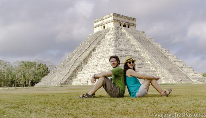 Pareja sentada frente a la famosa piramide de Chichen Itza, en México